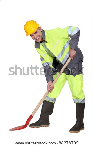 bricklayer all smiles with shovel against studio background - stock photo