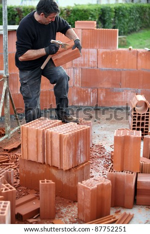 bricklayer building house - stock photo