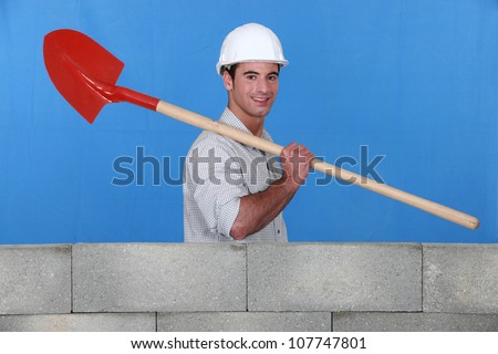 Bricklayer carrying a spade - stock photo