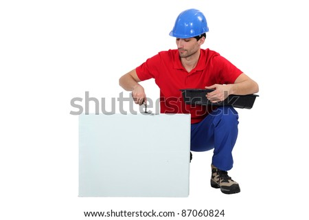 Bricklayer cementing a board left blank for your message - stock photo