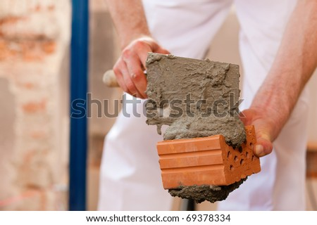 bricklayer laying bricks to make a wall, he is putting grout on top of a brick - stock photo