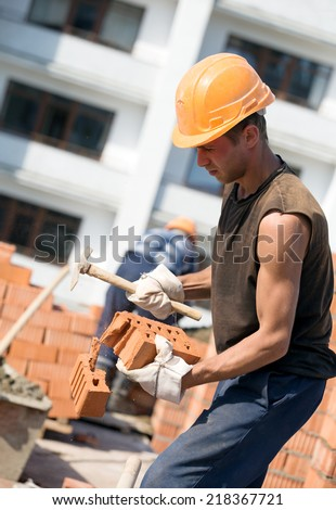 Bricklayer man worker cutting brick with masonry hammer during construction works - stock photo