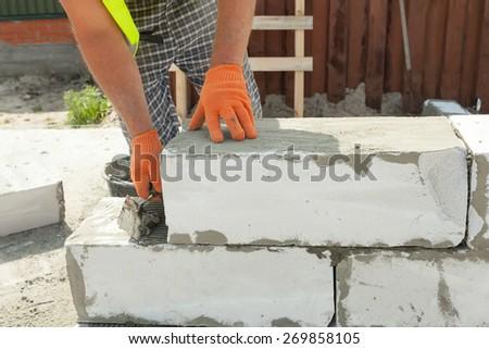 Bricklayer man worker in orange gloves installing block with trowel - stock photo