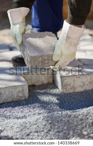 Bricklayer paving a street in a close up shot - stock photo