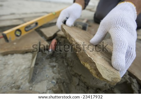 Bricklayer's hands in action with the level - stock photo