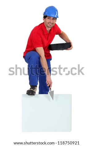 Bricklayer with a board left blank for your message - stock photo