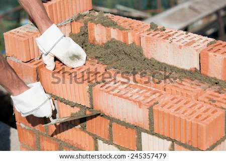 Bricklayer worker installing red blocks and caulking brick masonry joints exterior wall with trowel putty knife outdoor - stock photo