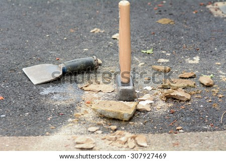 Bricklayers bolster chisel and lump hammer on floor
