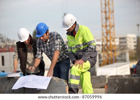 bricklayers outdoors with foreman - stock photo