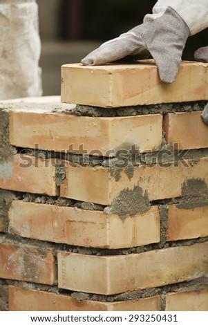 Bricklaying brick wall - stock photo