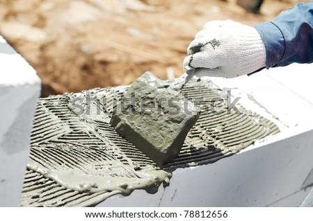 bricklaying construction process of cement mortar adding with trowel putty knife - stock photo