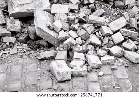 Bricks and rubble on a cobbled road in black and white - stock photo