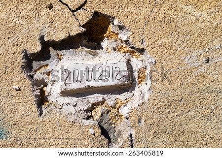 Bricks laid in an old wall with the date of the bookmark. Dirty concrete wall with cracks and scratches. Requires urgent repairs. Grungy concrete surface. Great background or texture for your project. - stock photo