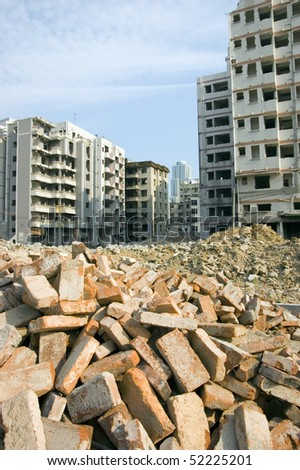 Bricks on first plan and old residential area ready for demolition in Chinese city Shenzhen. - stock photo