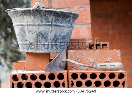 Bricks stacked trowel and cube in the work. Construction materials - stock photo