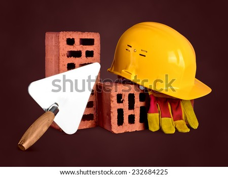 bricks, trowel and helmet on brown isolated background - stock photo