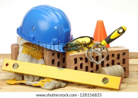 Bricks, trowel and helmet on work place - stock photo