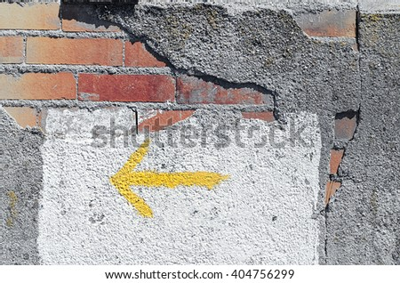 Bricks. Wall damaged. Building in ruins. Abstract background. Yellow arrow to the left. Vivid and vintage colors.