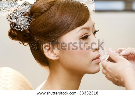 Bridal applying cosmetic with applicator. Make-up treatment. - stock photo