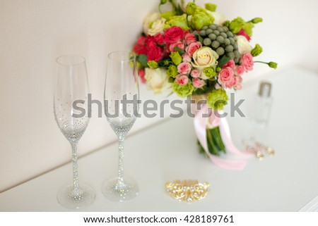 Bridal beautiful romantic bouquet of various flowers, glasses for champagne, in brilliant stones, a gold hairpin, earrings. Selective focus. - stock photo