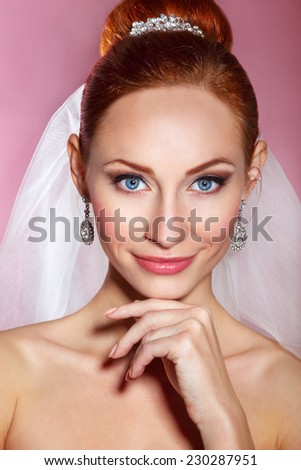 Bridal Beauty .Beautiful young woman with professional make up ..Bride's portrait on a pink background.Youth and Skin Care Concept.Girl with red hair - stock photo