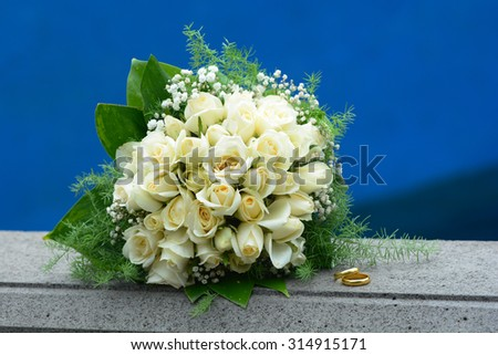 Bridal bouquet and weddind ringss isolated on bokeh background - stock photo