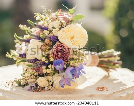 Bridal bouquet and wedding rings lying outdoors. - stock photo
