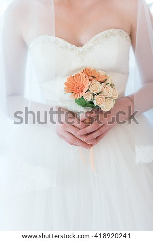 Bridal bouquet in hands of the bride. Bridal bouquet of artificial flowers. - stock photo
