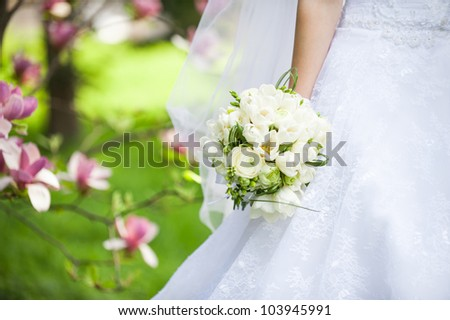 bridal bouquet in the hands of the bride in white wedding dress - stock photo