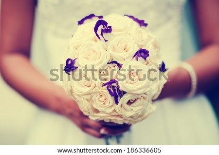 Bridal bouquet of flowers holding in hands by the bride - stock photo
