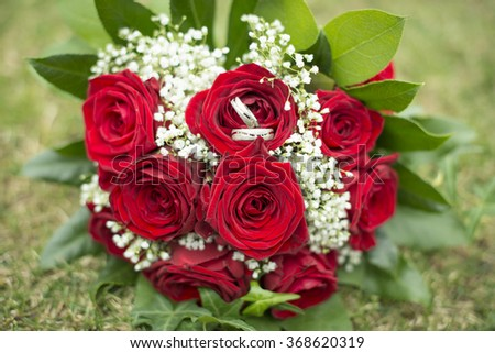 bridal bouquet of red roses on green grass, vintage filtered style - stock photo