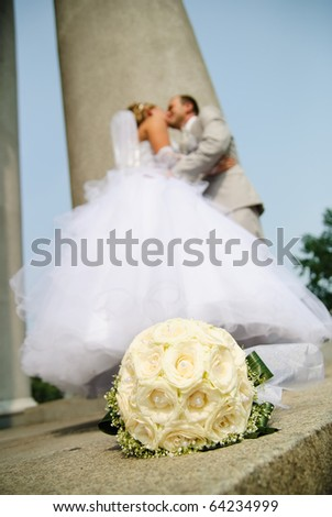 bridal bouquet of white roses and blurred newlyweds at background - stock photo