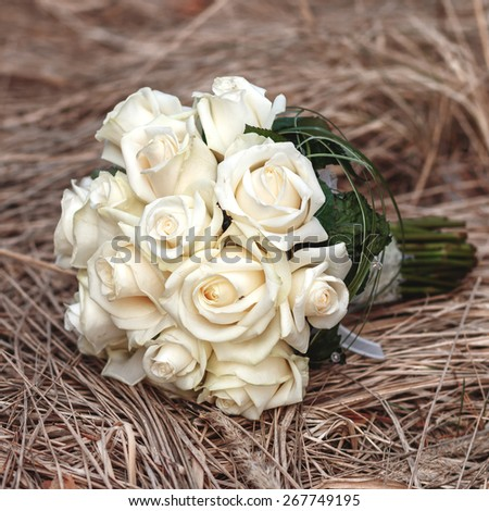 Bridal bouquet of white roses on a faded grass - stock photo