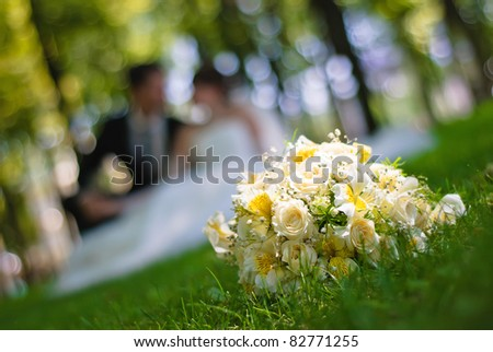 bridal bouquet of white roses on a green meadow and blurred newlyweds - stock photo