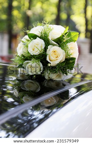 bridal bouquet of white roses on a white car - stock photo