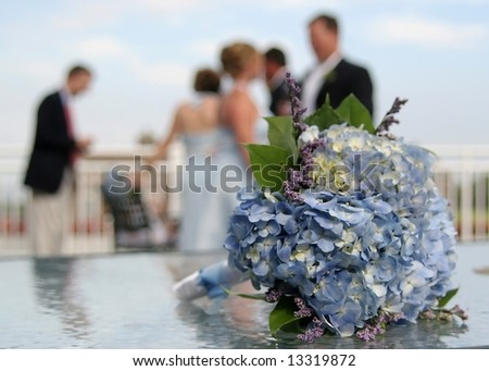 Bridal bouquet with wedding party in background, DOF focus on flowers - stock photo
