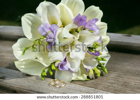 bridal bouquet with white callas and wedding rings - stock photo