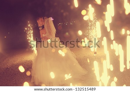 Bridal couple dancing sorrounding by fireworks - stock photo