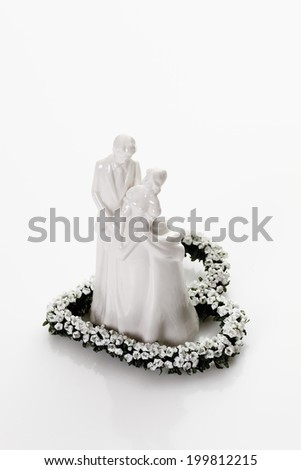 Bridal couple figurine standing on heart of flowers - stock photo