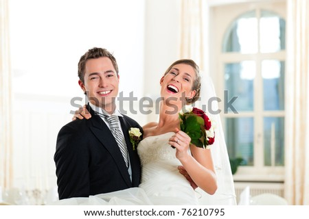 Bridal couple - groom is carrying his bride