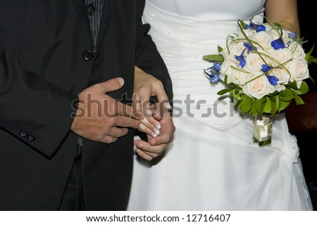 Bridal couple holding hands at the ceremony - stock photo