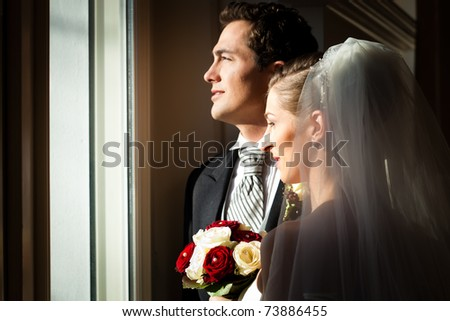 Bridal couple standing at the window at their wedding and looking outside