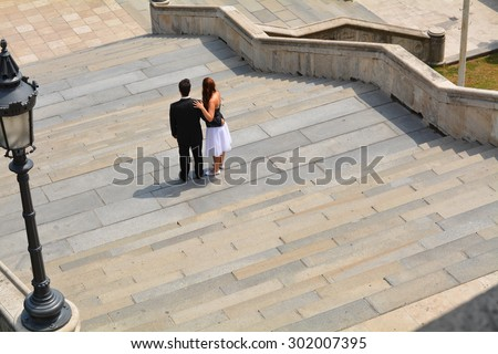 bridal couple standing on stairs to watch out