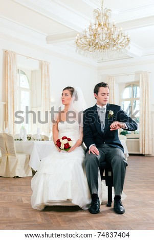 Bridal couple waiting for ceremony - he is already checking the time