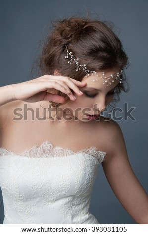 Bridal fashion, hairstyle and makeup. Brunette bride in wedding dress and beaded headpiece on gray backdrop. - stock photo
