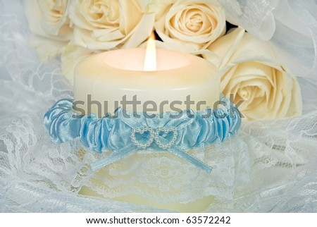 bridal garter wrapped around candle - stock photo