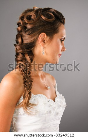 bridal hairdo with a plate on studio neutral background - stock photo