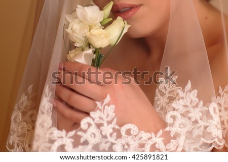 Bridal hands holding beautiful wedding boutonniere of white roses flowers near her face covered with elegant marriage veil  - stock photo