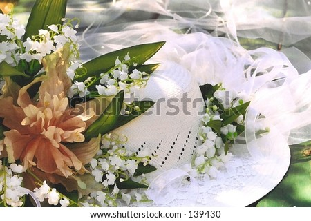 Bridal hat with flowers on picnic table - stock photo