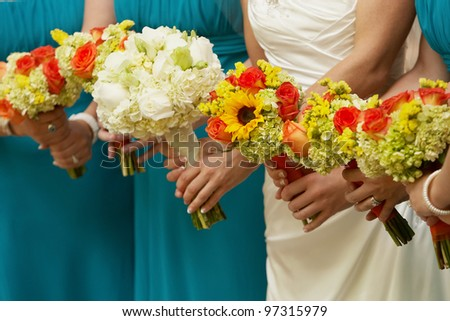 Bridal party holding colorful bouquets at wedding ceremony - stock photo